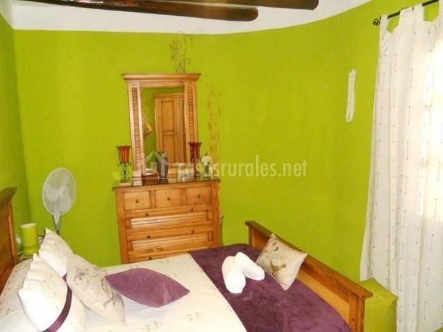 Dormitorio de matrimonio con paredes verdes
