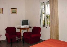 Dormitorio de matrimonio con su mesa con televisor