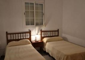 Dormitorio doble con cabeceros de madera y ventana central