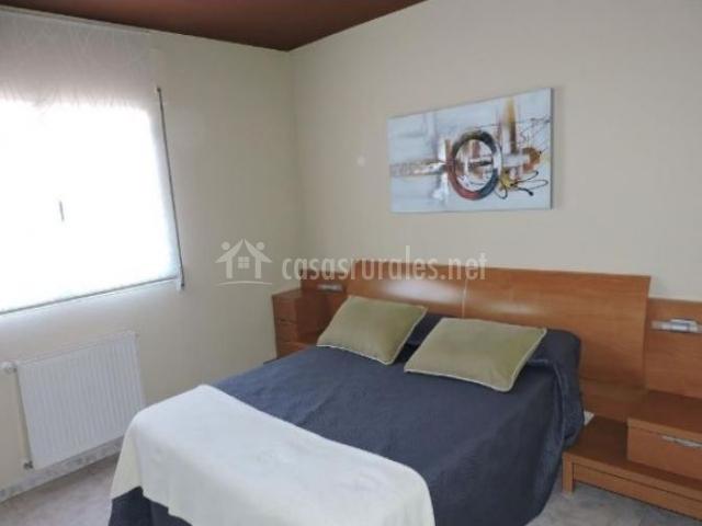 Dormitorio de matrimonio con estores en las ventanas