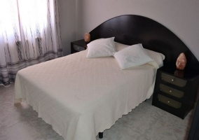 Dormitorio de matrimonio con cabecero en tonos oscuros