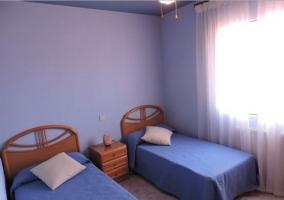 Dormitorio doble con paredes y colchas en azul