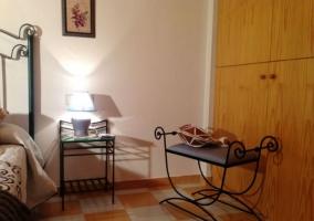 Dormitorio de matrimonio con armario de madera y mobiliario en forja
