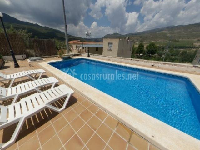 Acceso a la piscina del complejo con hamacas en blanco