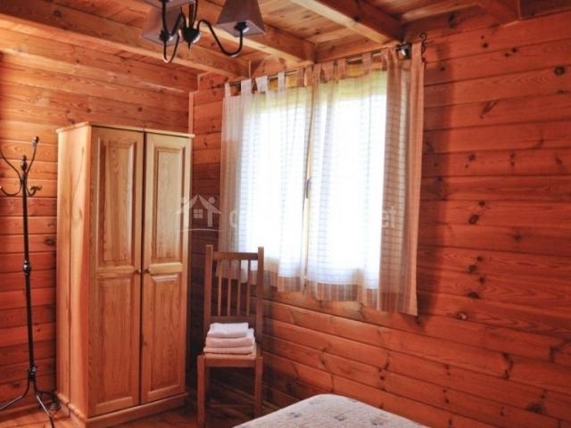 Dormitorio de matrimonio con silla y toallas