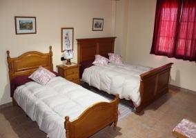 Dormitorio doble con cabeceros de madera y mesilla en el centro