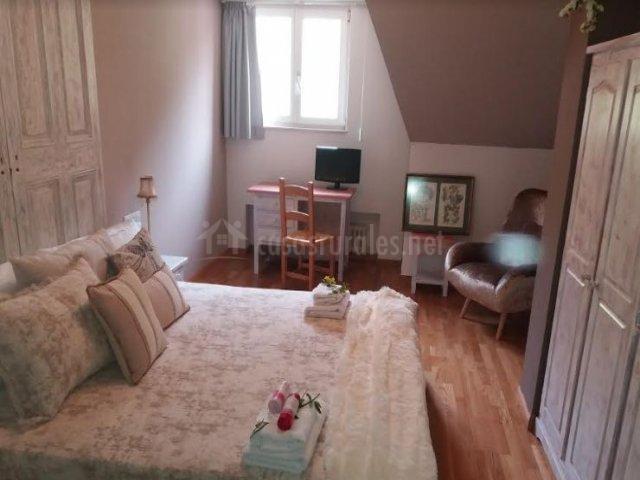 Dormitorio de matrimonio amplio con originales muebles