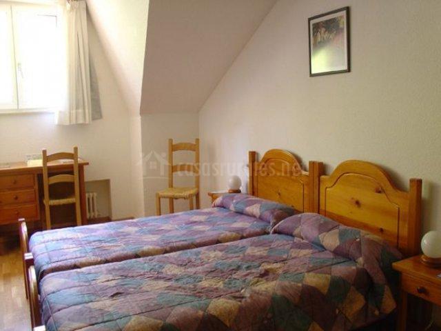 Dormitorio doble con un par de camas y escritorio bajo la ventana