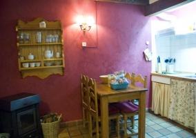 Cocina y comedor con mesa de madera y alacena