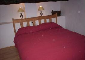 Dormitorio de matrimonio con lamparillas tras el cabecero