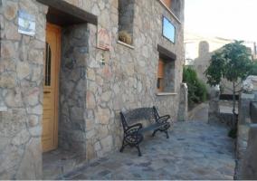 Acceso principal a la vivienda con puerta de madera y muro