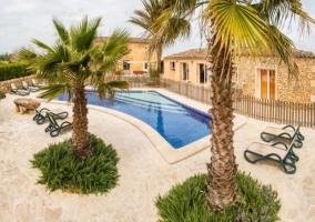 Acceso principal al apartamento con piscina y hamacas