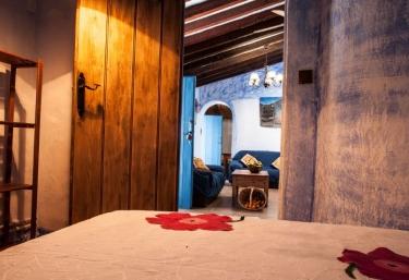 Dormitorio doble con cama de matrimonio y paredes de estuco