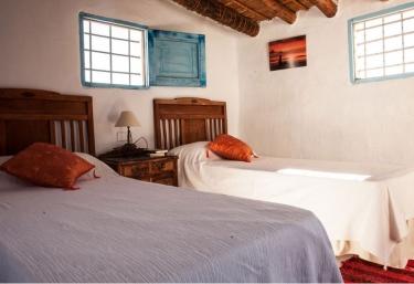 Dormitorio doble con colchas en color blanco y mesilla en el centro