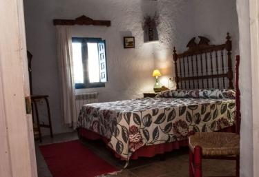 Dormitorio de matrimonio con silla y alfombras