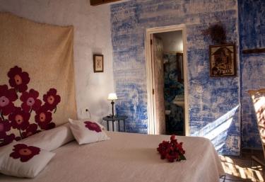 Dormitorio de matrimonio con detalle de flores sobre la colcha