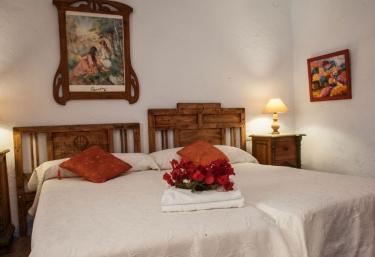 Dormitorio doble con cojines tapizados en tonos rojos