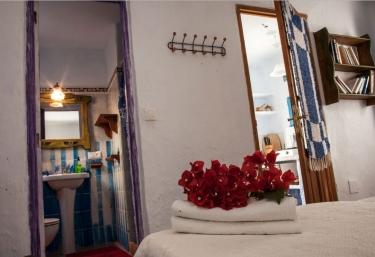 Dormitorio doble con cojines tapizados y aseo