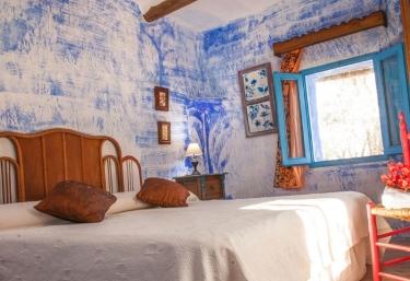 Dormitorio doble con paredes de estuco azul
