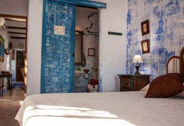 Dormitorio doble con paredes de estuco y aseo