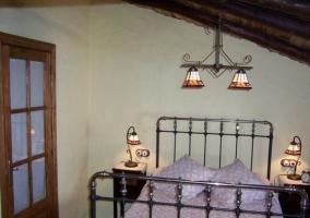 Dormitorio de matrimonio abuhardillado con vigas de madera