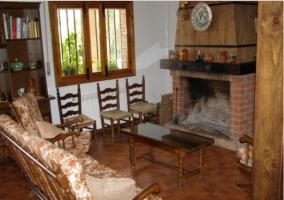 Sala de estar en planta baja con chimenea junto a la ventana