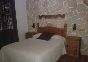 Dormitorio de matrimonio con robusto cabecero de madera