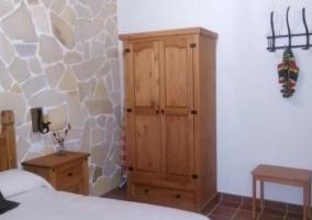 Dormitorio de matrimonio con robusto cabecero y armario