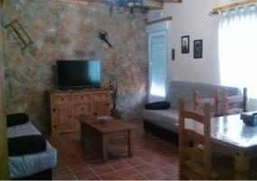 Sala de estar con televisor en el mueble central de madera