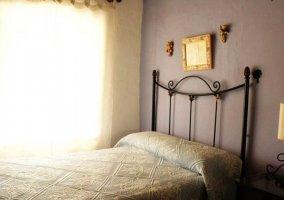 Dormitorio doble con mesilla en el centro y colcha