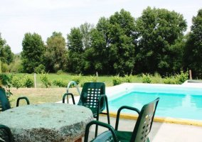 Vistas de la piscina del complejo junto a la mesa de piedra