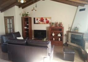 Sala de estar con chimenea en esquina y techos de madera