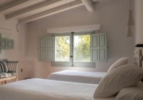 Dormitorio doble con vigas de madera lacadas en blanco