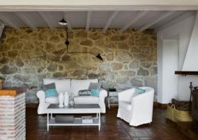 Sala de estar con la chimenea y las paredes en piedra