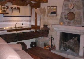 Sala de estar con chimenea comunicada con la cocina