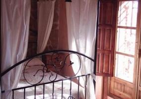 Dormitorio de matrimonio con dosel y telas