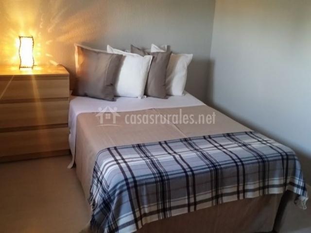 Dormitorio de matrimonio con manta de cuadros