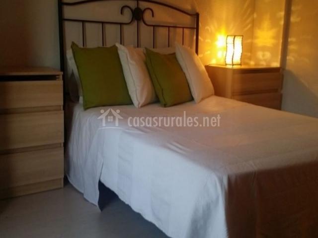Dormitorio doble con cojines en blanco y verde