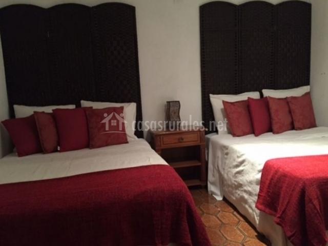 Dormitorio doble con mantas de color burdeos