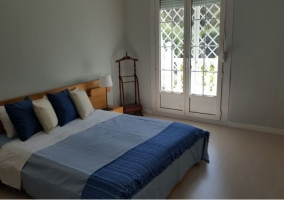 Dormitorio de matrimonio con cojines en azul y blanco
