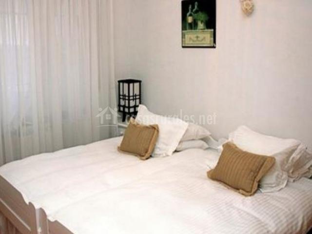 Dormitorio doble con cojines en tonos marrones