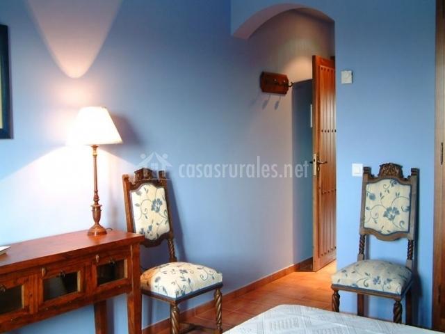 Dormitorio doble en azul con sillas tapizadas