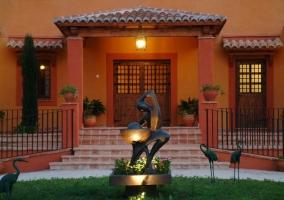 Acceso con escaleras y escultura
