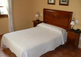 Dormitorio de matrimonio con cabecero de madera y colchas en blanco