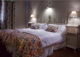 Dormitorio doble con cortinas y manta de flores