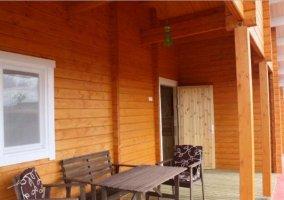 Vistas del porche con mesa y silla en madera