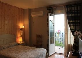 Dormitorio de matrimonio con cuadros y ventana