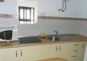 Cocina con mesa y armarios en beige