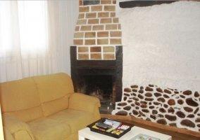 Sala de estar con chimenea integrada y suelo de madera