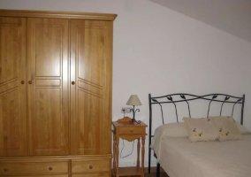 Dormitorio de matrimonio con armario de madera y mesillas